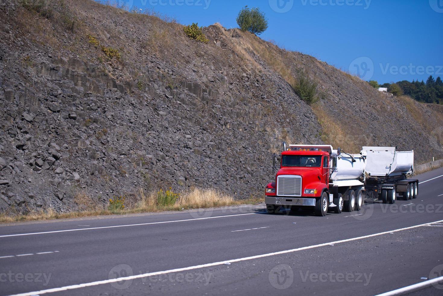 caminhão semi vermelho e dois reboques no caminho alto foto