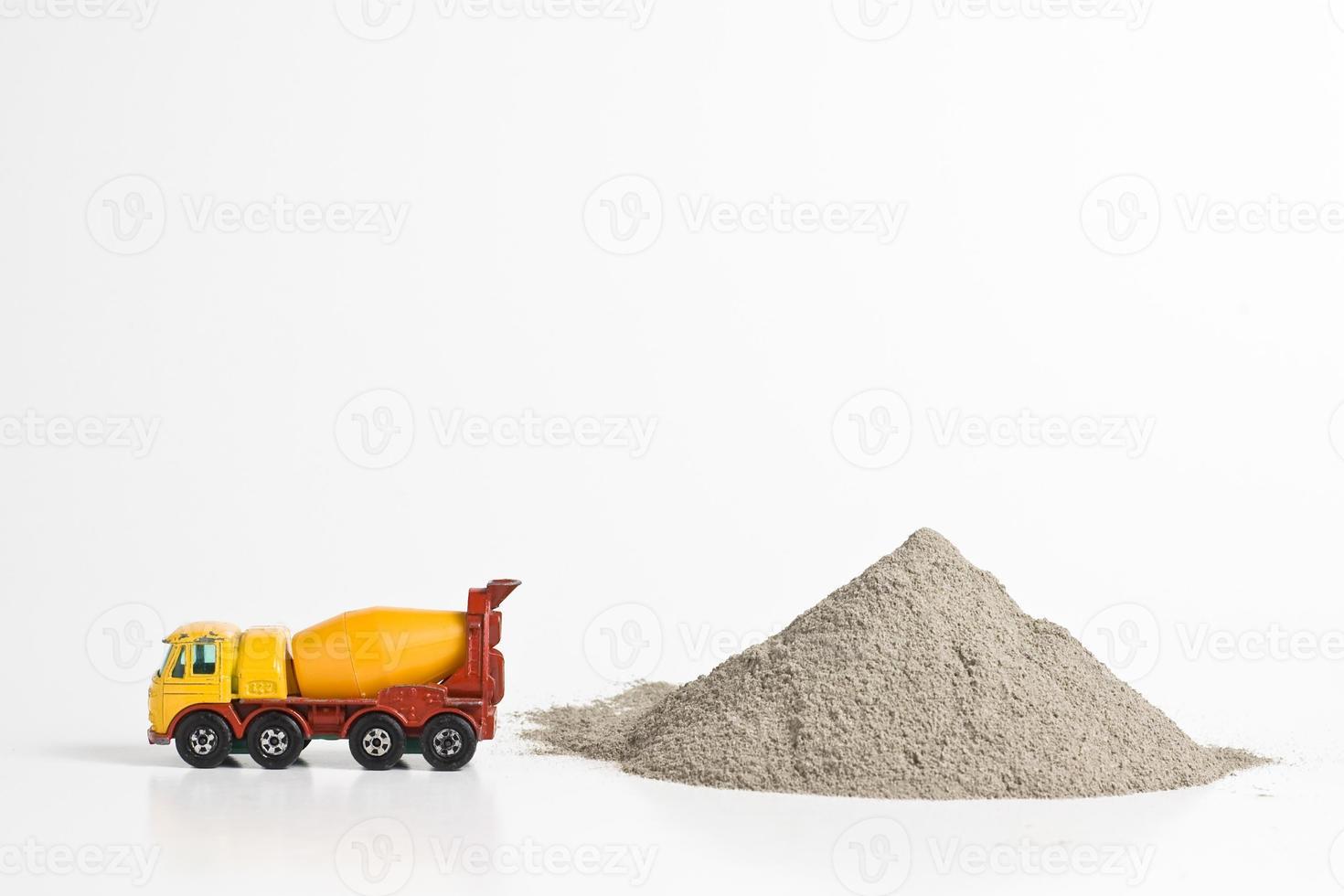 caminhão de concreto em miniatura ao lado da pilha de cimento em pó foto