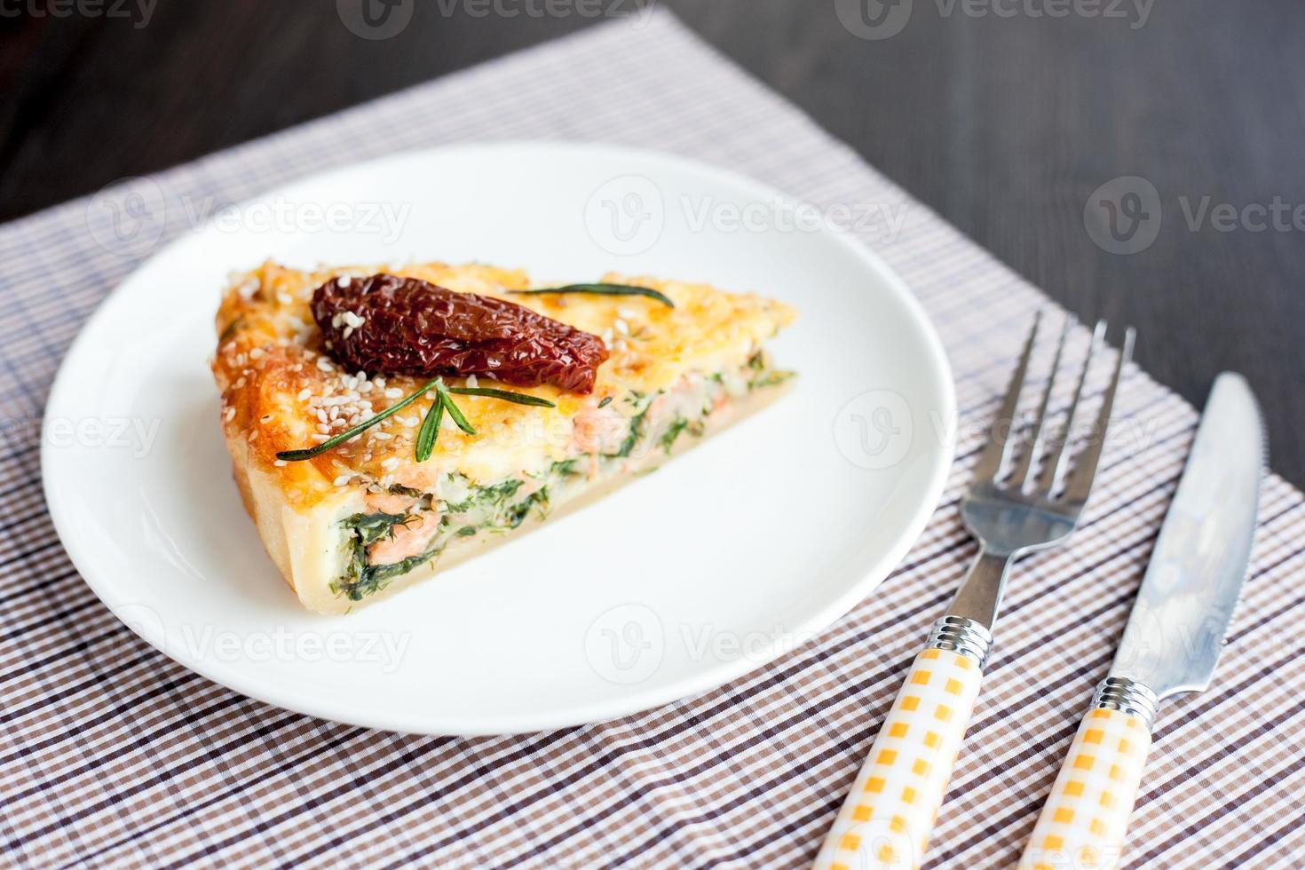 pedaço de torta com espinafre e peixe salmão foto