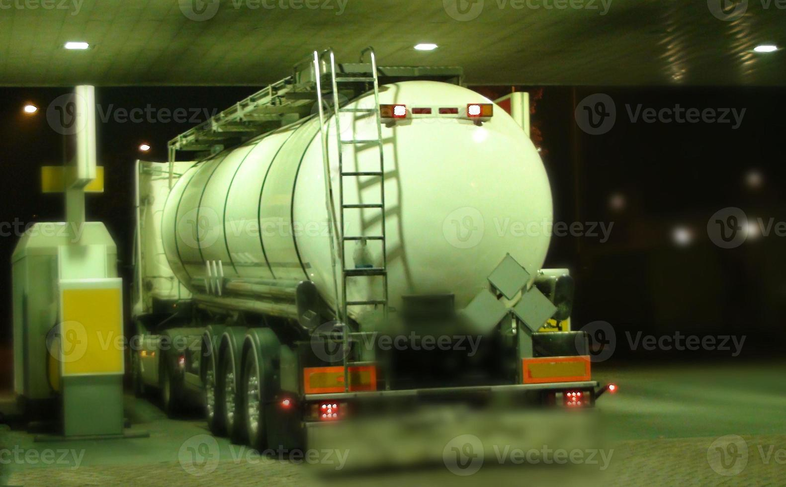 caminhão-tanque estacionado no posto de gasolina no meio da noite foto