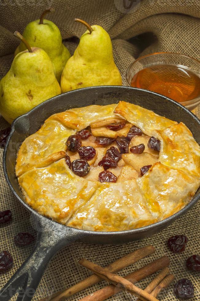 torta de pêra e cereja quente em uma frigideira de ferro fundido foto
