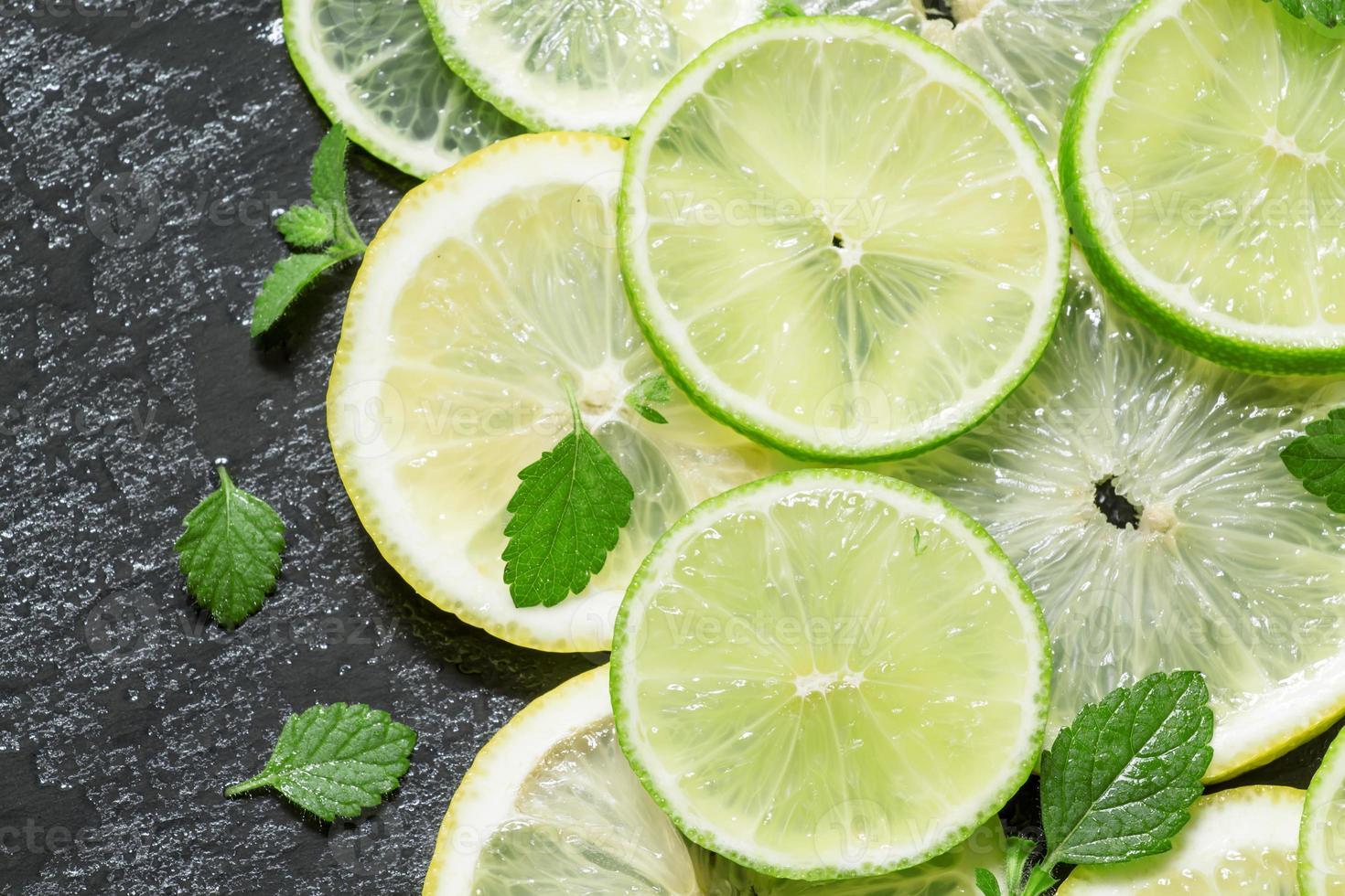 fatias de limão, limão e folhas de hortelã em um fundo escuro foto