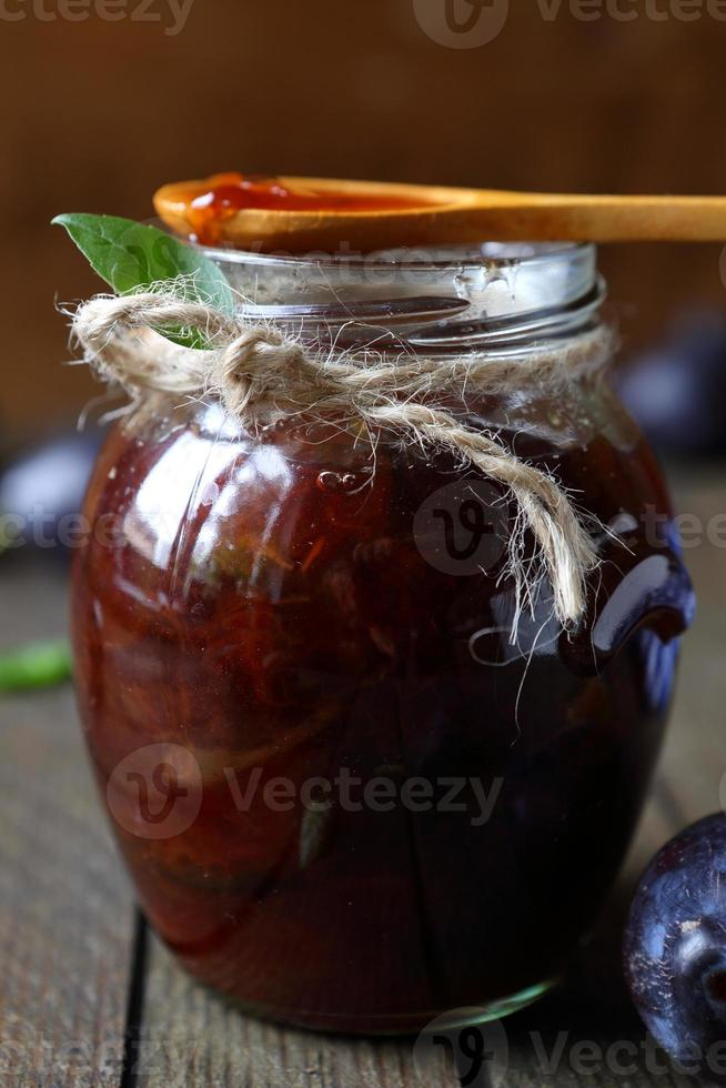 geléia de ameixa em uma jarra transparente e colher de pau foto