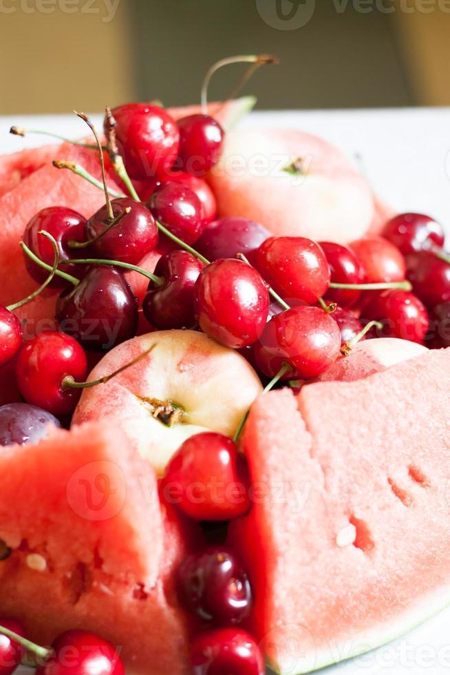 frutas suculentas brilhantes: melancia, cerejas e pêssegos foto