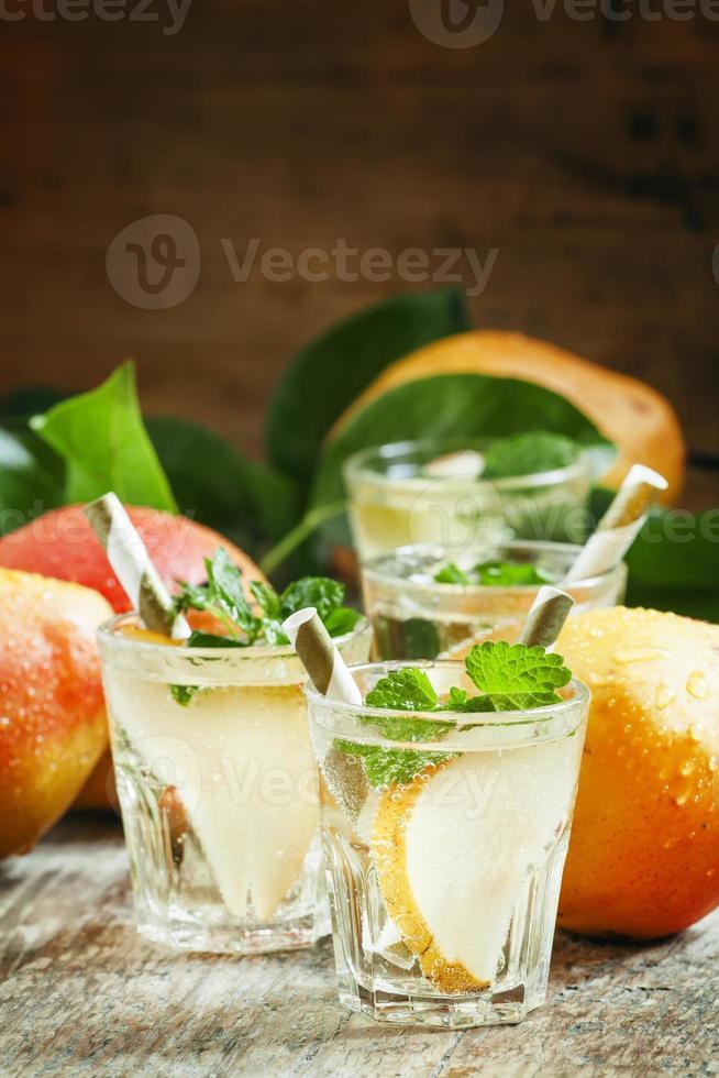 coquetel de pera com refrigerante, fatias de frutas e hortelã foto