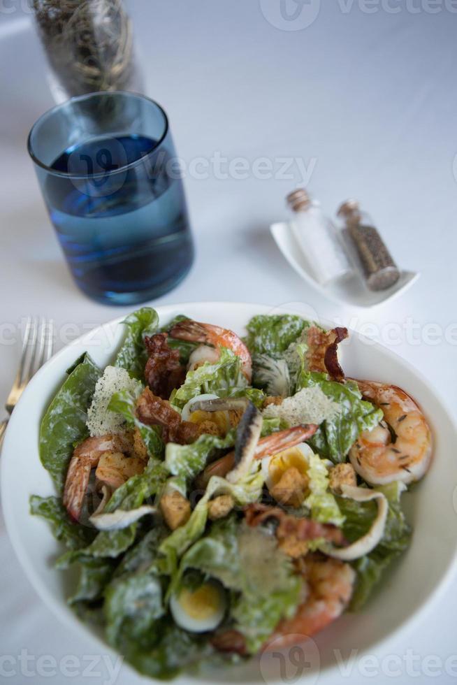 salada caesar de camarão com ovo de codorna, pancetta e batatas fritas com parmesão. foto