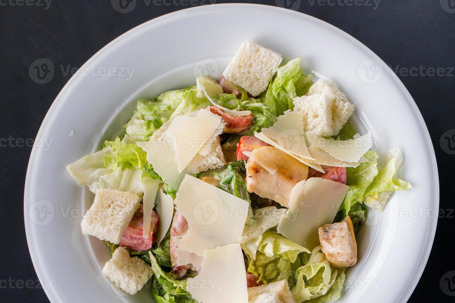 salada caesar com frango e verduras na mesa de madeira foto