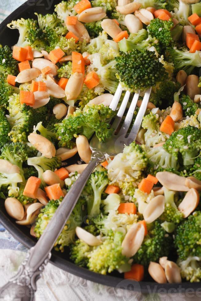 salada com brócolis, cenoura e amendoim closeup vertical top vi foto
