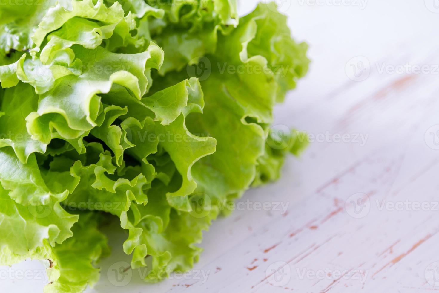 salada de alface, fundo branco de madeira foto