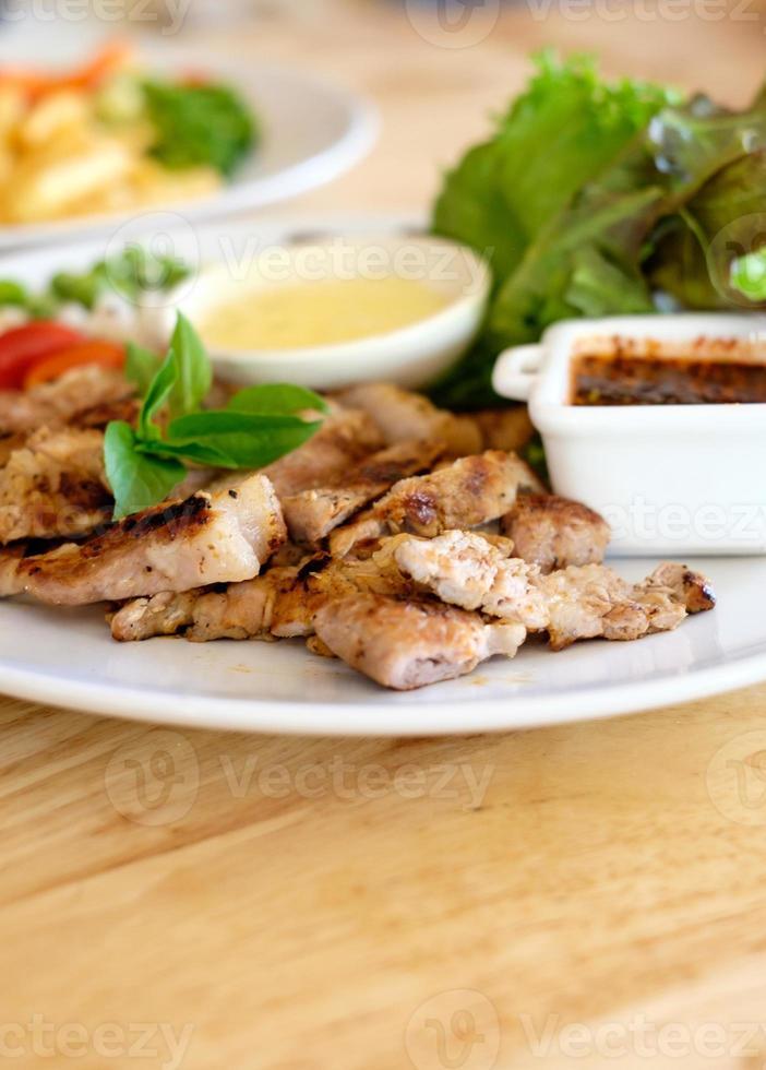 bife grelhado carne de porco e salada, foco suave foto