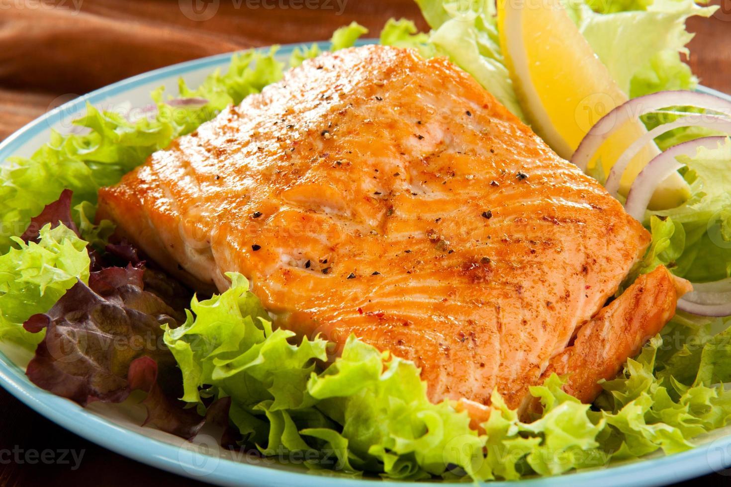 salmão fresco em uma pilha de alface foto