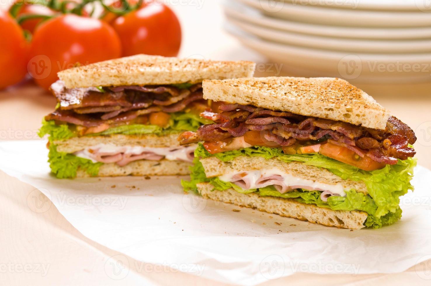 dois sanduíche no papel de embrulho terreno de volta tem tomates foto