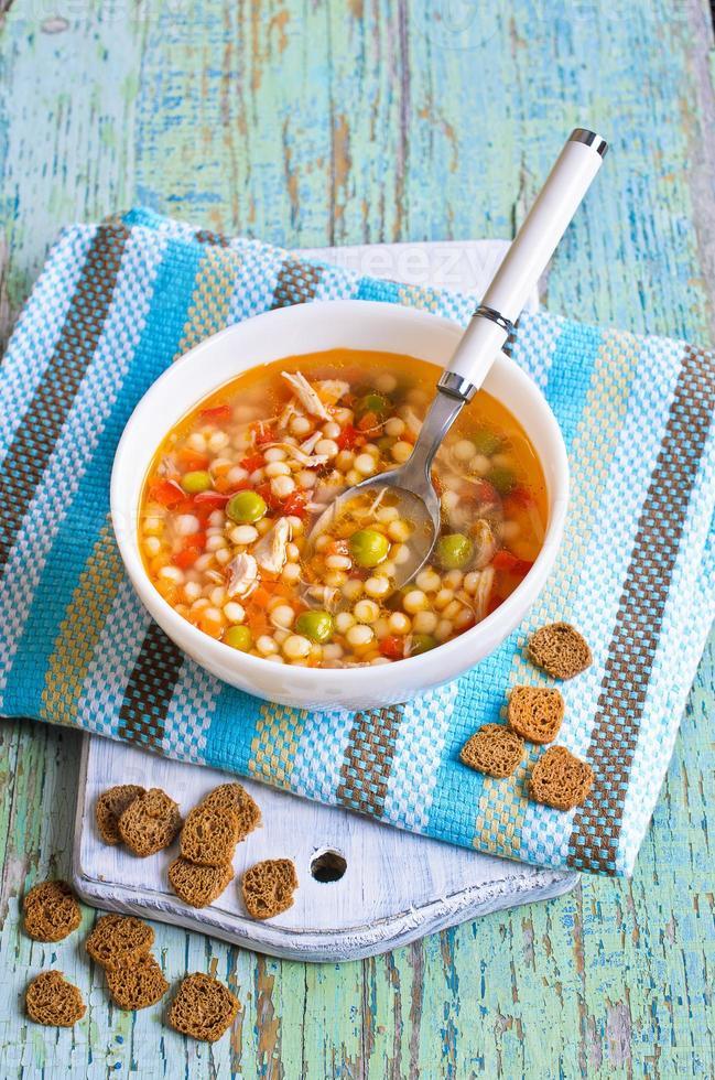 sopa com macarrão pequeno, legumes e pedaços de carne foto