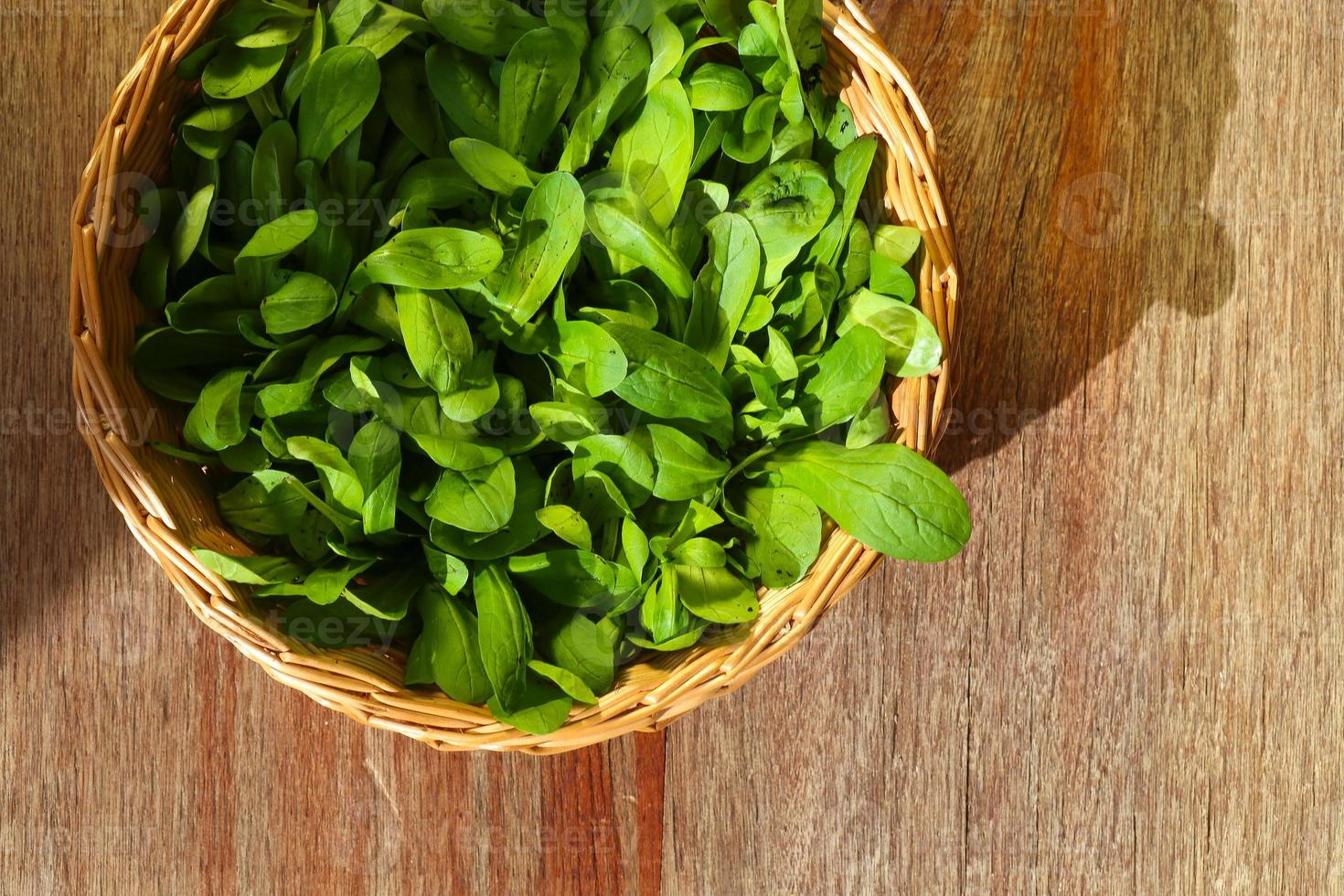 cesta de vime com salada de milho verde folhas foto