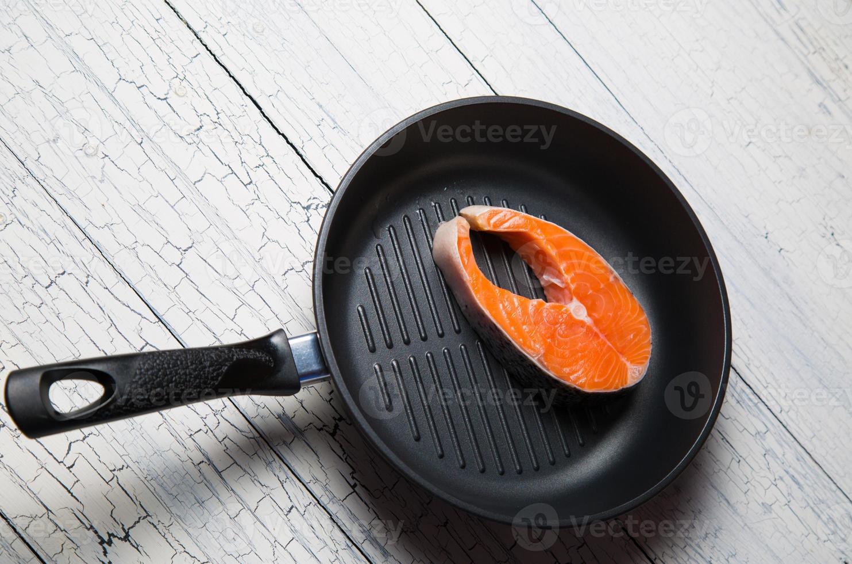 bife de salmão fresco na panela de grelhar foto