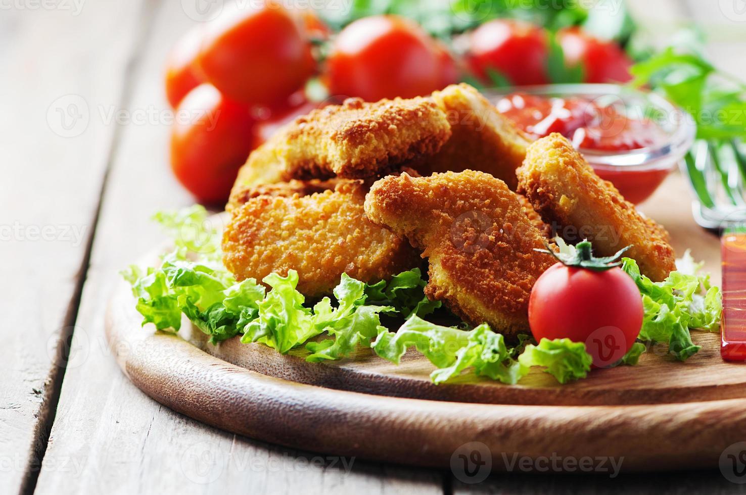 nuggets de frango em cima da mesa de madeira foto