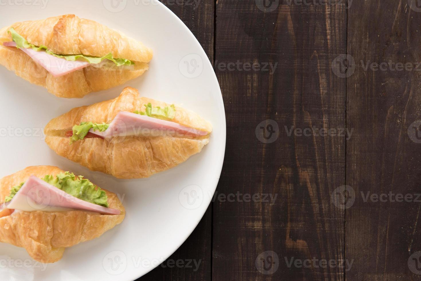 croissant com presunto de parma e alface na mesa de madeira foto