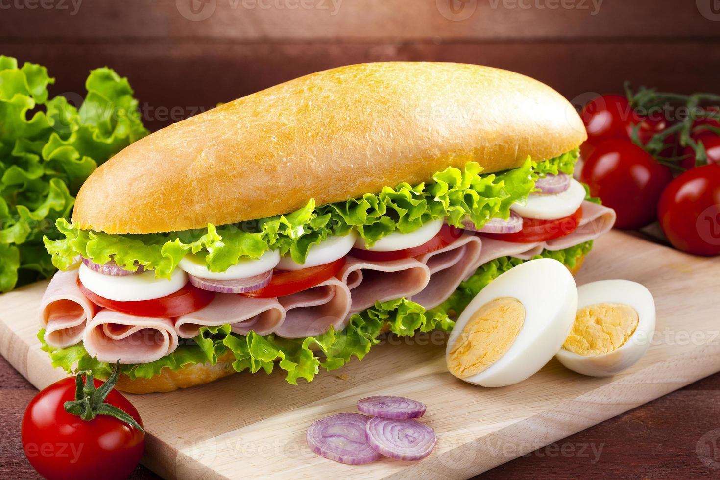 sanduíche grande com presunto, queijo e legumes foto