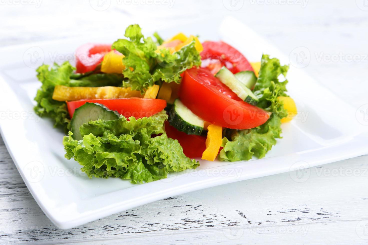 salada de legumes fresca em fundo branco de madeira foto