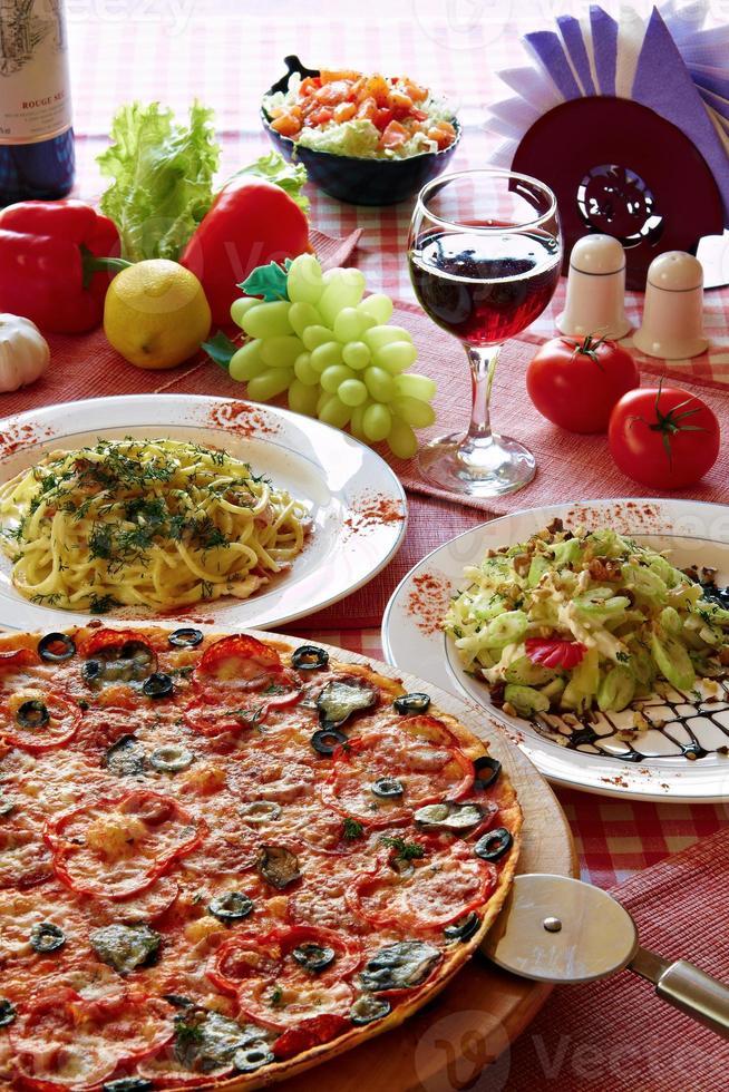 cenário de comida italiana clássica com pizza, macarrão, salada e vinho foto
