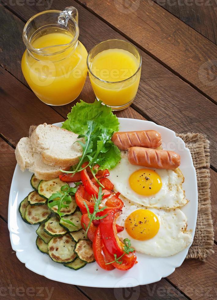 café da manhã inglês - ovos fritos, salsichas, abobrinha e pimentão foto