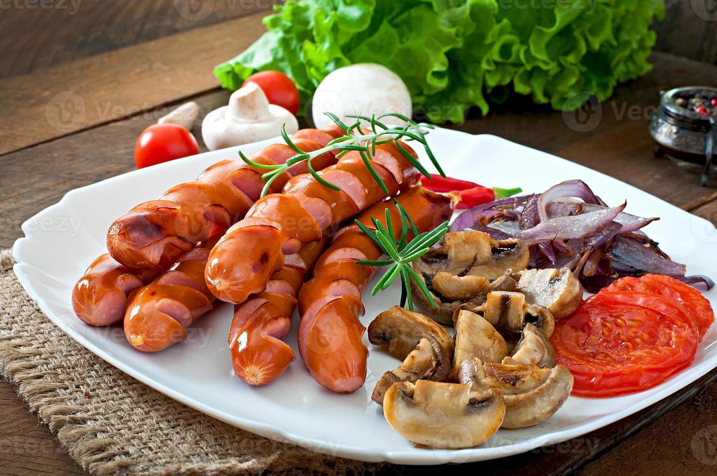 salsichas fritas com legumes em um prato branco foto