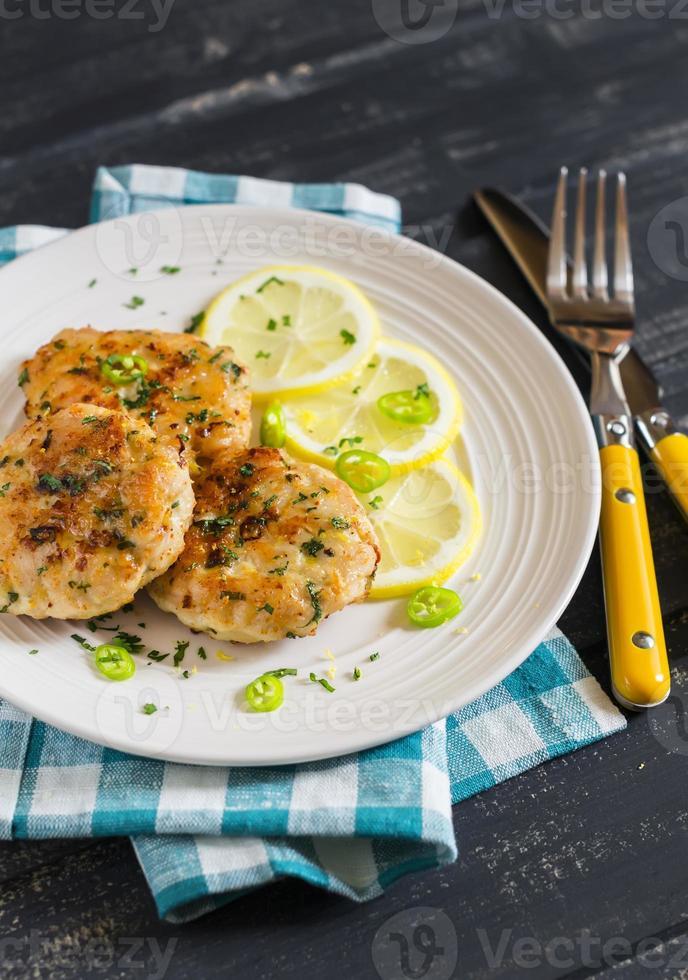 costeletas de frango com limão e ervas em um prato branco foto