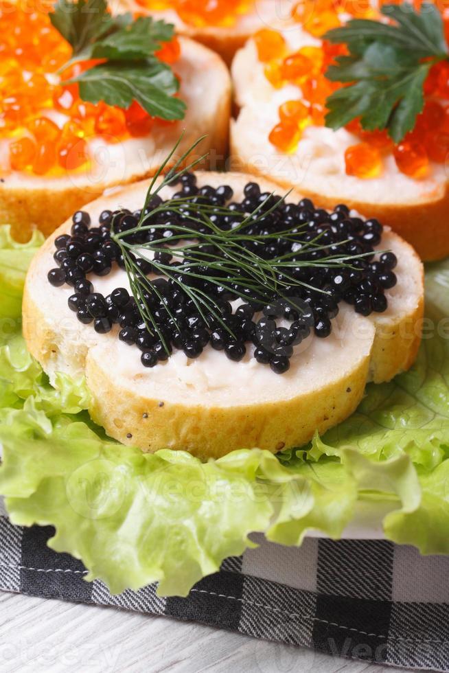 sanduíches com caviar de peixe vermelho e preto com alface foto