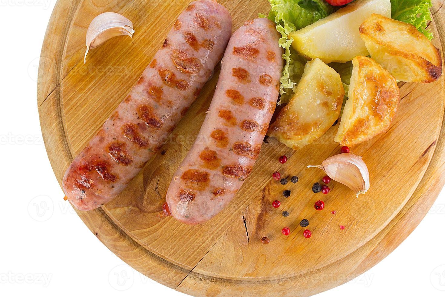 saborosas salsichas grelhadas na placa de madeira foto