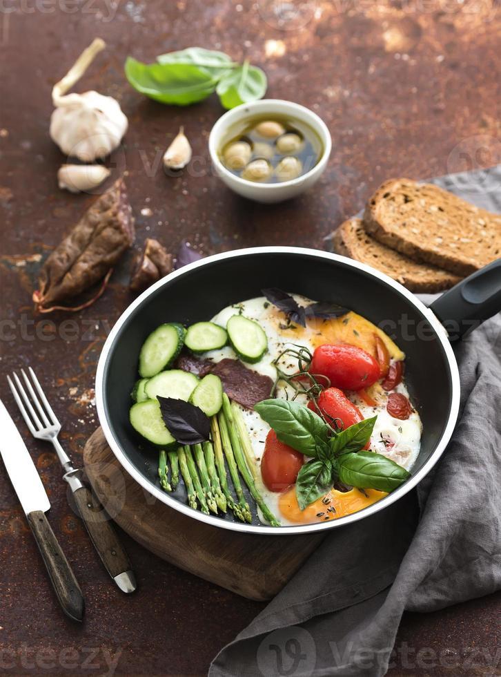 panela de ovos fritos, salame, aspargos, tomate cereja com pão foto