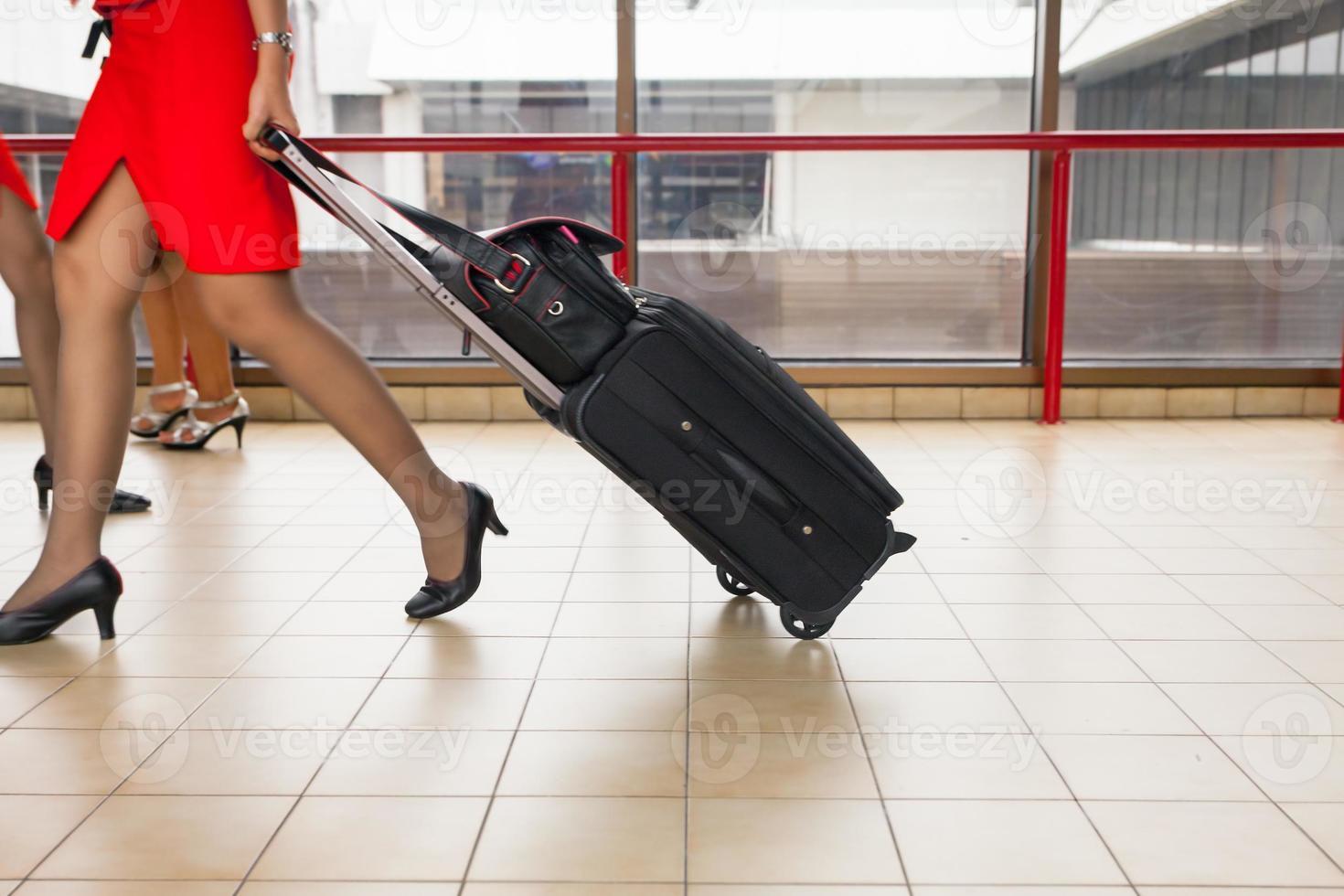 mulheres carrega sua bagagem no aeroporto foto