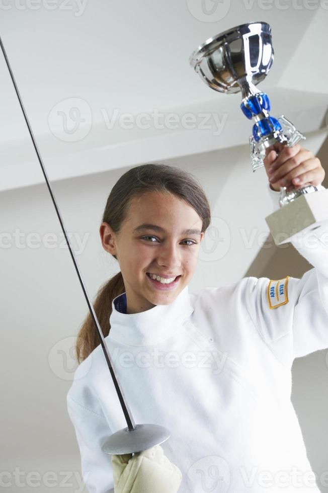 menina sorridente, segurando o troféu de esgrima foto
