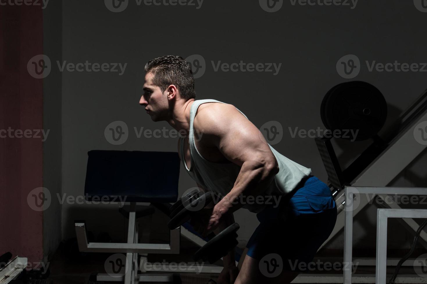 homem no ginásio exercitar tríceps com halteres foto