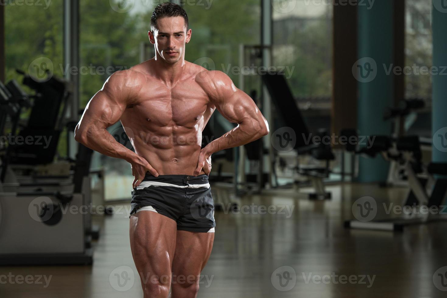homens musculares flexionando os músculos foto