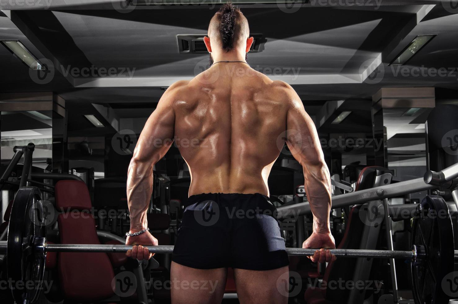 homem musculoso, levantando alguns halteres pesados foto