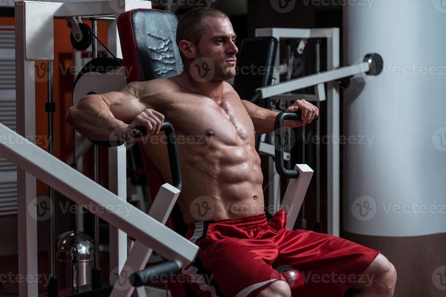 jovem fisiculturista fazendo exercício de peso pesado para o peito foto