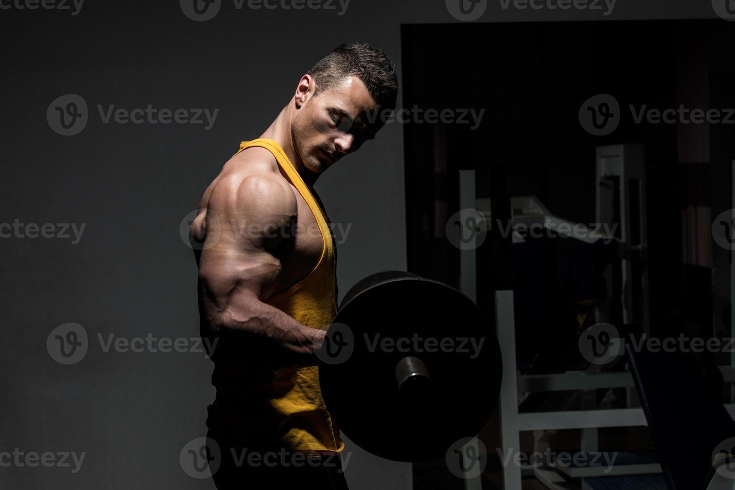 jovem fazendo exercício de peso pesado para bíceps foto
