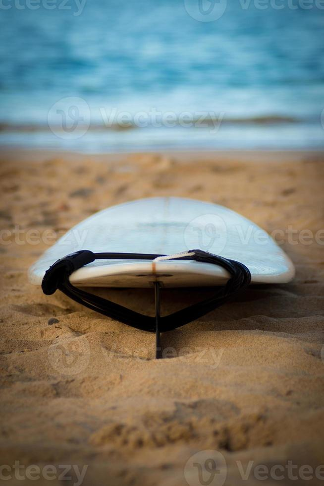 prancha de surf com trela na areia, oceano no fundo foto