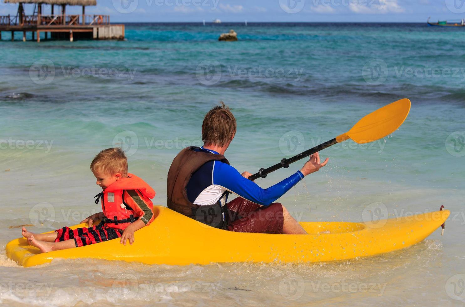 pai e filho, caiaque no oceano tropical foto