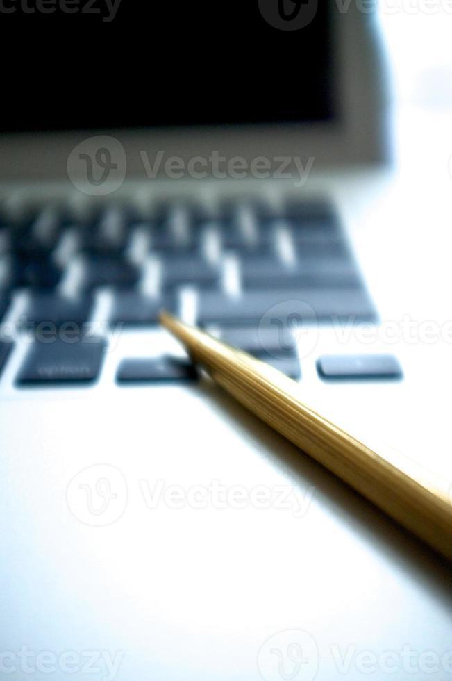 laptop e caneta esferográfica foto