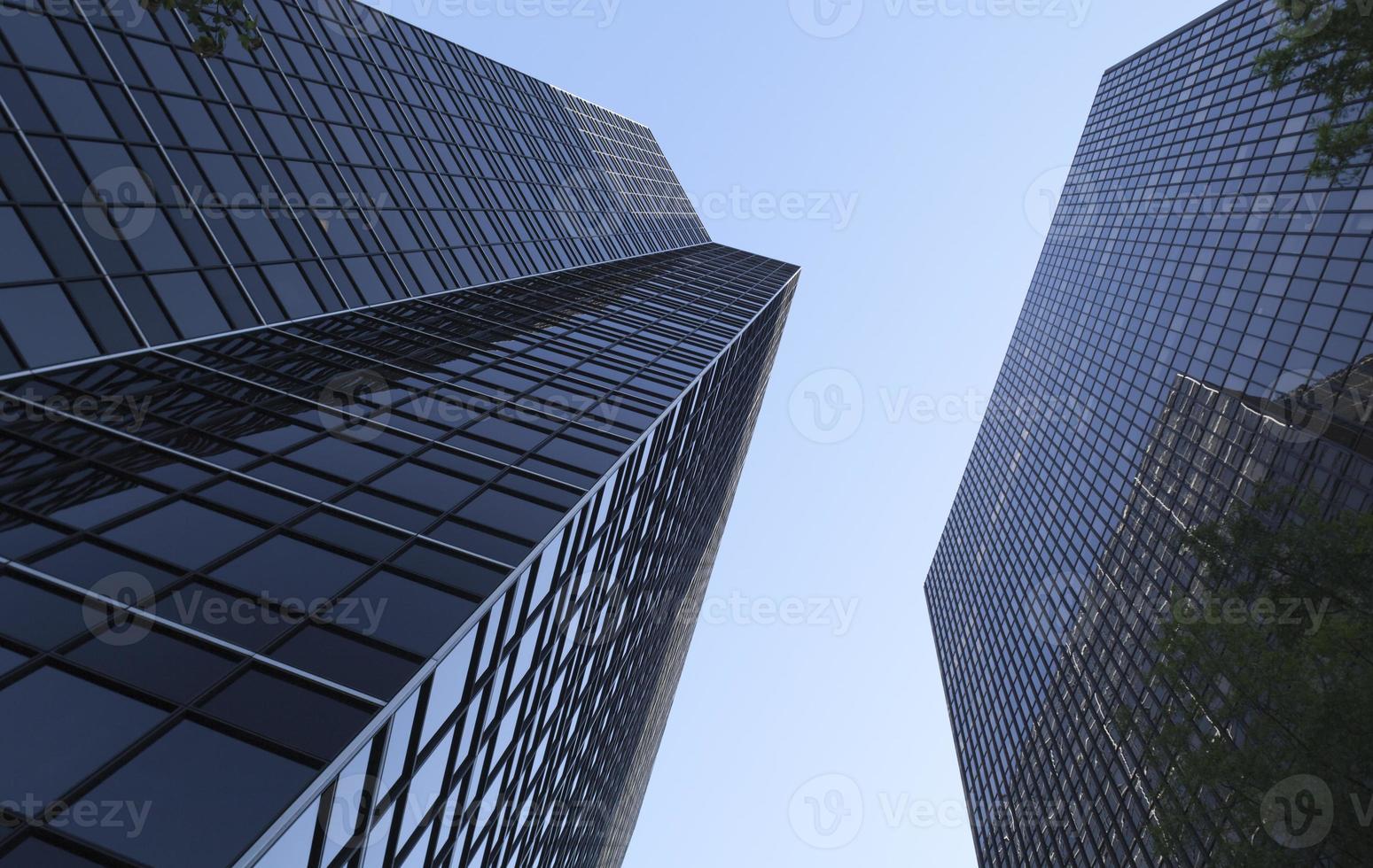 torres de escritórios modernos de aço e vidro sob o céu azul foto