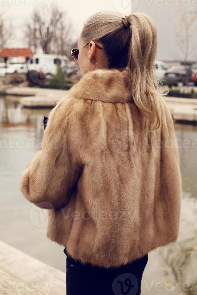 garota com cabelo loiro, vestindo casaco de pele de luxo foto