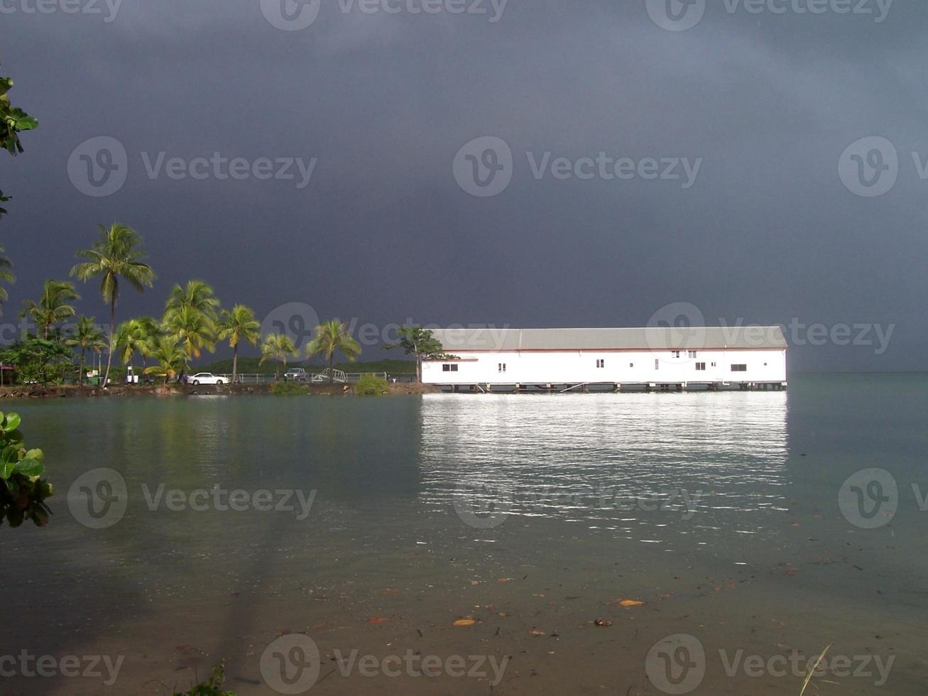 céu tempestuoso sobre casa de barco branco foto