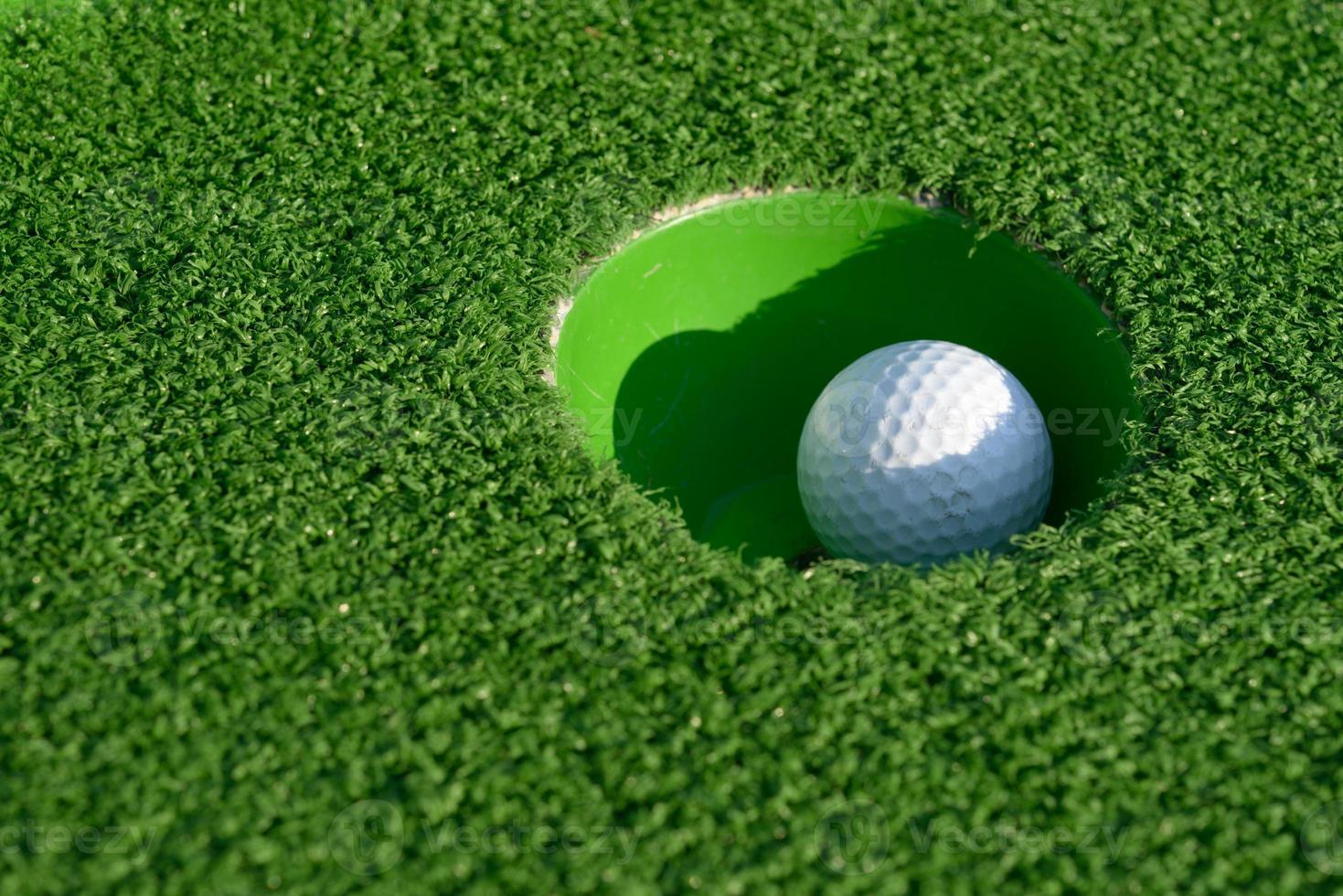 bola de minigolfe em um buraco foto