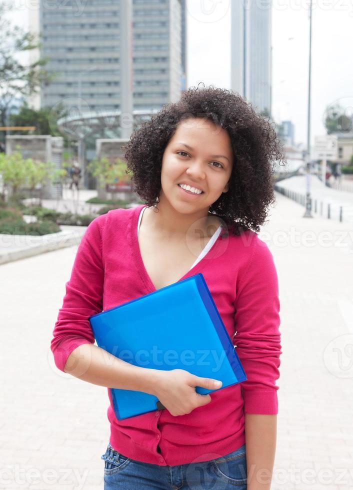 aluna afro-americana em pé na cidade foto