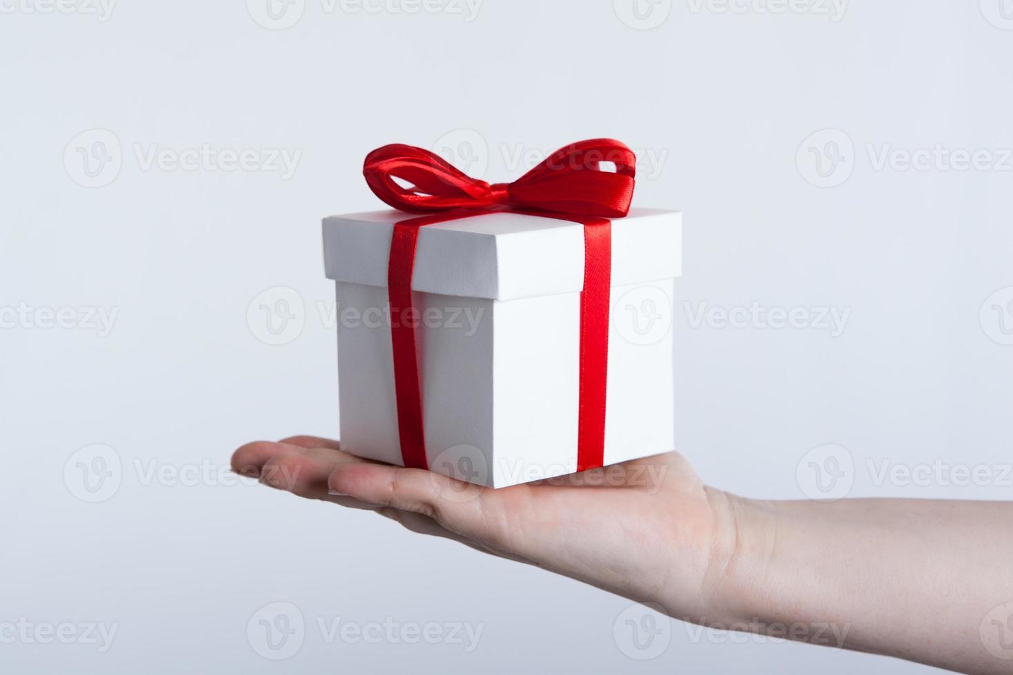 caixa de presente branca com fita vermelha na mão foto