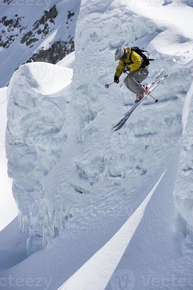 esquiador salta da borda do cume de neve na geleira. foto