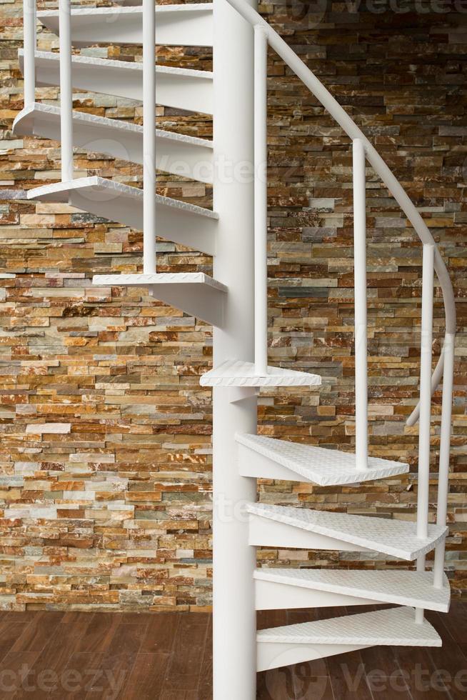 escada em espiral branca na parede de pedra foto