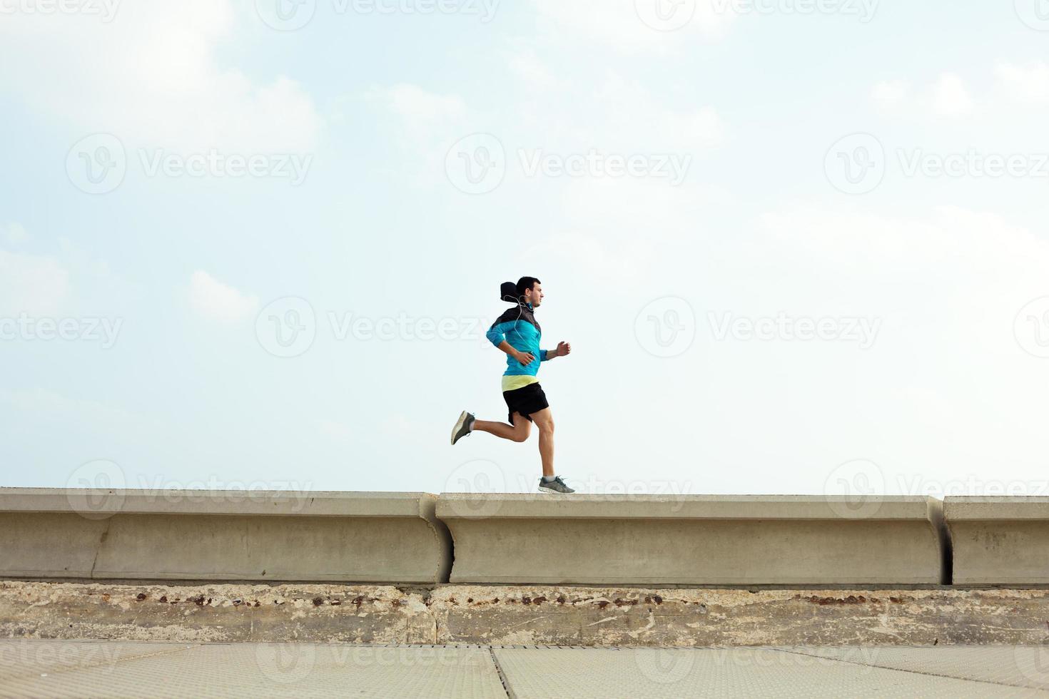 esportista correndo na borda de concreto foto