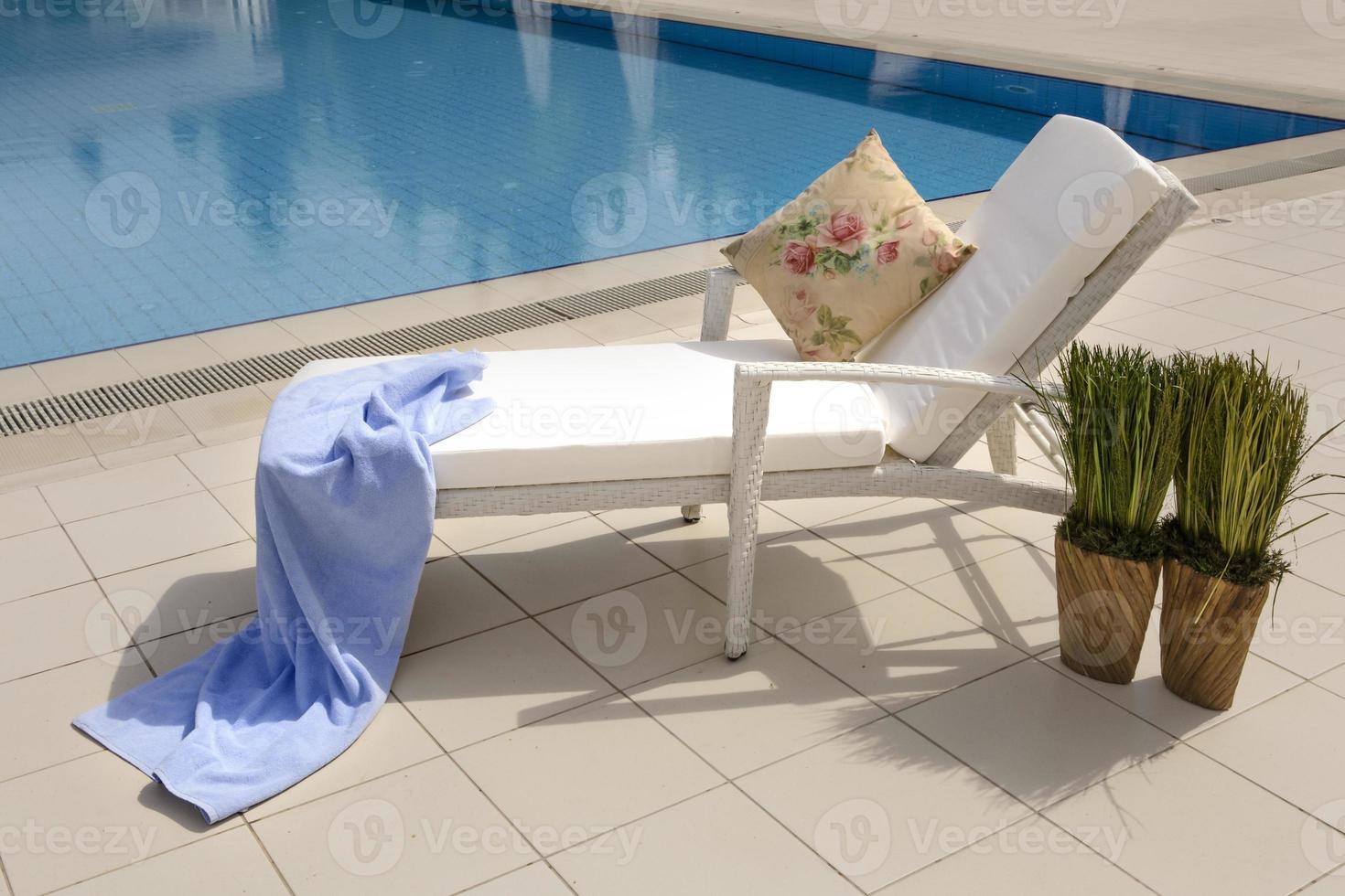 espreguiçadeira ao lado da piscina em um hotel de luxo foto